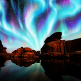 Aurora over lagoon. Multicolor aurora over lagoon and red rock Royalty Free Stock Images