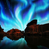 Aurora over lagoon. Multicolor aurora over lagoon and red rock Royalty Free Stock Photography
