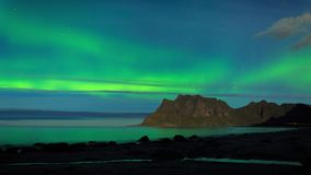 Aurora over the sea timelapse. Aurora over the sea at Utakleiv beach, Lofoten Islands, Norway stock video