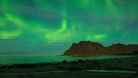 Aurora over the sea timelapse. Aurora over the sea at Utakleiv beach, Lofoten Islands, Norway stock video footage
