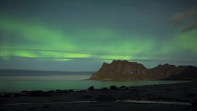 Aurora over the sea at Utakleiv beach, Lofoten Islands, Norway. Aurora over the sea timelapse at Utakleiv beach, Lofoten Islands, Norway stock footage