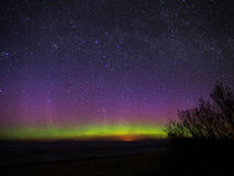 Aurora polar lights and magic stars over sea. Universe stars and polar lights over sea Stock Photos