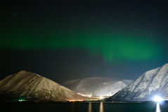 Aurora polaris above a settlement. Ribbons of Aurora polaris above the tops of mountains Stock Photography