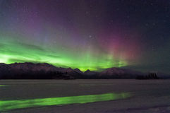Aurora Reflection. The Northern green and purple lights that reflected onto the ice Royalty Free Stock Photos