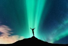Aurora borealis and silhouette of a happy woman Royalty Free Stock Photo