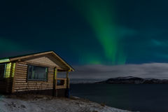 Aurora and a small wooden house Stock Photography