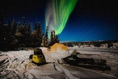 Aurora Snowmobile. Aurora lights of Yellowknife, NWT at Raven Tours Night picture with long exposure to capture the Aurora Night sky, in forest during winter on Stock Photography