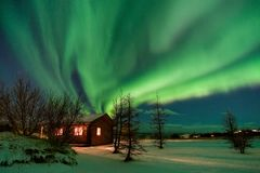 Aurora sobre a casa de campo em Islândia foto de stock