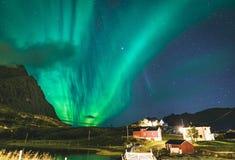 Aurora sobre casa roja tradicional del pescador en Noruega, islas de Lofoten Aurora boreal en las islas de Lofoten, Noruega starr foto de archivo libre de regalías