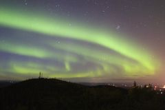 Aurora swirling over town royalty free stock photography