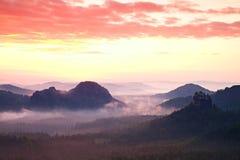 Aurora vermelha Aurora enevoada no montes bonitos Os picos dos montes estão colando para fora do fundo nevoento, a névoa é vermel imagem de stock