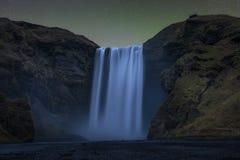 Auroraglühen über Skogafoss-Wasserfall stockbild