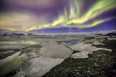 Auroral över glaciärlagun Jokulsarlon i Island arkivbilder