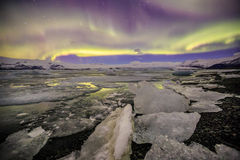 Auroral över glaciärlagun Jokulsarlon i Island arkivfoton
