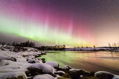 Auroras at wintry riverbank. Colorful auroras appeared at riverbank on a wintry night in Finland Stock Photo
