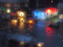 Aurumn rain droplets on window glass with traffic lights. Royalty Free Stock Photos