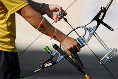 AUS bow 01. Hands hold an archery bow and arrow ready to aim at a target Stock Photography