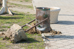 Aus Erde heraus einen defekten Wheeliebehälter mit Betonsockel zerrissen Lizenzfreie Stockfotografie
