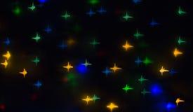 Aus Fokus und unscharfen farbigen Sternformlichtern auf schwarzem Hintergrund heraus Lizenzfreies Stockbild