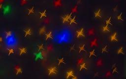 Aus Fokus und unscharfen farbigen Sternformlichtern auf schwarzem Hintergrund heraus Stockbilder