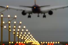 Aus Fokuspassagierflugzeug und Rollbahnlichtern heraus Stockbilder