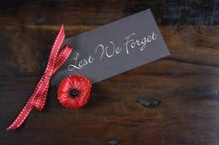 Aus Furcht, dass wir vergessen, bereitete rote Poppy Lapel Pin Badge auf Dunkelheit Holz auf Stockbild