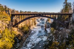 Ausable Chasm Bridge - Keeseville, NY. Iron bridge over Ausable River at Ausable Chasm, a 2 mile gorge in the Adirondacks of Upstate New York known as the Grand Royalty Free Stock Images