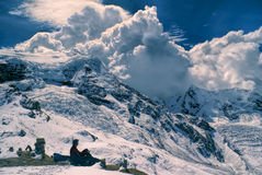 Ausangate, Andes. Young hiker sitting in south american Andes in Peru, Ausangate with dramatic clouds forming above the mountains stock photo
