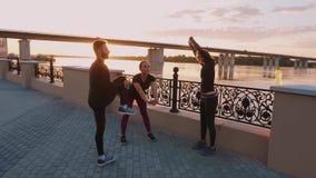 Ausarbeitende Leute Mann und Frau, die Übung gegen einen schönen Sonnenuntergang ausdehnend tut stock video footage