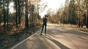 Ausbildung eines Athleten auf den Rollenschlittschuhläufern Biathlonfahrt auf die Rollenskis mit Skipfosten, im Sturzhelm Herbst stock video