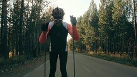 Ausbildung eines Athleten auf den Rollenschlittschuhläufern Biathlonfahrt auf die Rollenskis mit Skipfosten, im Sturzhelm Herbst stock footage