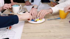 Ausbildung für Angestellte Büroangestellte nehmen Süßigkeit von einer Platte am Tisch, Handnahaufnahme Aufschrift der roten Farbe stock video