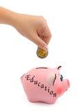 Ausbildung und Hand der Piggy Querneigung mit Münze Lizenzfreie Stockfotografie