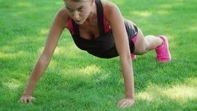 Ausbildungsstoß der Eignungsfrau ups Übung auf Gras im Sommerpark stock footage