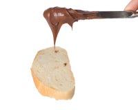Ausbreitende Schokoladensahne auf Brotscheibe Lizenzfreie Stockbilder
