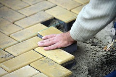 Ausbreitender Plattefußboden des Bauarbeiters Stockfotografie