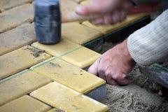 Ausbreitender Plattefußboden des Bauarbeiters Stockbild