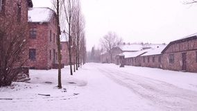 Auschwitz Birkenau, German Nazi concentration and extermination camp. Barracks in falling snow Royalty Free Stock Photos