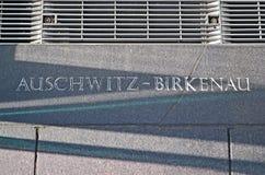 Auschwitz - birkenau, meddelandecloseup på stenväggen, Royaltyfri Foto