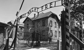 Auschwitz Concentration Gate, ARBEIT MACHT FREI sign. Sunny day on the July 7th, 2015. Black and white. Krakow, Poland Royalty Free Stock Photos