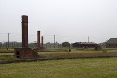 Free Auschwitz Holocaust Memorial Museum - Brick Chimneys The Remains Of Wooden Barracks Which Housed Prisoners Maintained As A Memori Stock Photo - 182567660
