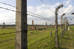 Auschwitz II -Birkenau Extermination camp outdoors behind a barbed wire fence wall Royalty Free Stock Images
