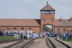 The security tower at the entrance to Auschwitz Birkenau concentration camp with group of kids on March of the Living. stock photo