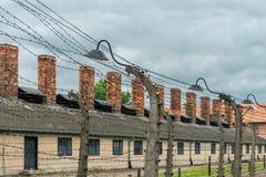 Auschwitz Polen - Augusti 12, 2017: territoriet av en koncentrationslägernärbild av försett med en hulling - binda, som hög spänn Fotografering för Bildbyråer