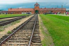 Auschwitz, Polonia - 12 de agosto de 2017: carriles con la entrada principal al campo de concentración de Auschwitz Birkenau Imagen de archivo libre de regalías