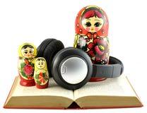 Auscultadores com as bonecas do russo no livro aberto Fotografia de Stock Royalty Free