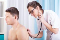 Auscultating ασθενής γιατρών Στοκ φωτογραφία με δικαίωμα ελεύθερης χρήσης
