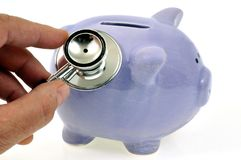 Auscultation of a piggy bank with a stethoscope. Tax control concept with a piggy bank with a stethoscope in closeup on white background stock photography