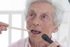 Auscultation senior with tongue depressor Royalty Free Stock Image
