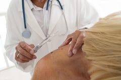 AUSCULTATION SENIOR WOMAN FOR SKIN PROBLEM. Dermatologist focus on senior women beauty spot Royalty Free Stock Images